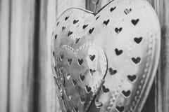 Corazón decorativo del metal en la pared de madera Imágenes de archivo libres de regalías