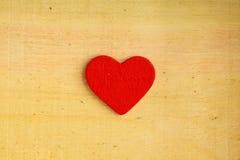 Corazón decorativo rojo en textura de madera del fondo Fotografía de archivo libre de regalías