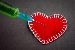 Corazón decorativo una jeringuilla con un veneno verde imagen de archivo