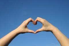 Corazón del amor con las manos en cielo azul imagenes de archivo