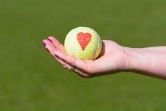 Corazón del amor de la pelota de tenis que es celebrado por el jugador de tenis Fotografía de archivo libre de regalías