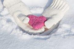 Corazón del amor del día de tarjetas del día de San Valentín en manos de la manopla imagenes de archivo