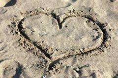 Corazón del amor drenado en arena Imagen de archivo