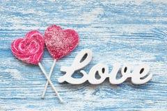 Corazón del caramelo con AMOR del texto 3D en tableros de madera Imagen de archivo