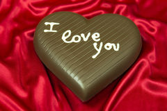 Corazón del chocolate en el satén rojo Fotografía de archivo libre de regalías