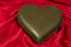 Corazón del chocolate en el satén rojo imagen de archivo