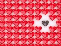 Corazón del chocolate entre una pila de corazones rojos Fotos de archivo libres de regalías