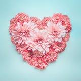 Corazón del color en colores pastel hecho de flores rosadas preciosas en el fondo de los azules turquesa, visión superior Imagenes de archivo