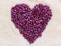 Corazón del día de tarjetas del día de San Valentín hecho de Bean Isolated rojo en Brown Sackclot Imagenes de archivo