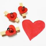 Corazón del dibujo con tres mariquitas en los clips de la forma del corazón Imágenes de archivo libres de regalías
