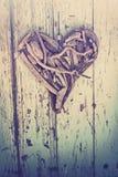 Corazón del Driftwood en la pared de la vendimia imagenes de archivo