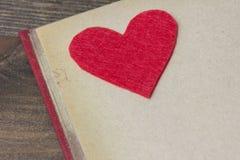 Corazón del fieltro del rojo en el libro Fotografía de archivo libre de regalías