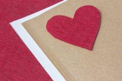 Corazón del fieltro del rojo en el libro Imagenes de archivo