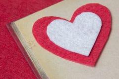Corazón del fieltro del rojo en el libro Imagen de archivo