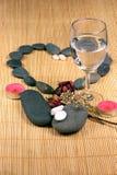Corazón del guijarro, vidrio, y flores secadas en el fondo de la rota Imágenes de archivo libres de regalías