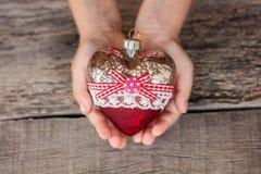 Corazón del juguete del árbol de navidad en las manos de un niño Año Nuevo Navidad Fondo de madera Foto de archivo libre de regalías