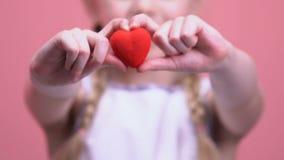 Corazón del juguete de la demostración de la niña en el primer de la cámara, la caridad y el concepto de la amabilidad metrajes