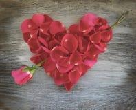Corazón del pétalo de Rose en viejo fondo de madera foto de archivo libre de regalías