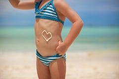 Corazón del primer pintado por la crema del sol en poco Foto de archivo libre de regalías