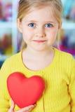 Corazón del rojo del control de la niña Foto de archivo libre de regalías