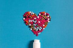 Corazón del símbolo del medicamento de las píldoras del color en fondo azul Concepto de la medicina de la creatividad imágenes de archivo libres de regalías