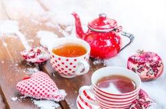 Corazón del vintage, taza caliente de té en la nieve, tetera roja Imagen de archivo libre de regalías