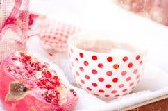 Corazón del vintage, taza caliente de té en la nieve, tetera roja Foto de archivo