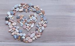 Corazón dentro de un círculo de guijarros coloridos en superficie de madera CCB Fotografía de archivo libre de regalías
