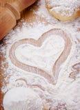 Corazón dibujado con la harina en la tabla de cocina Imagenes de archivo