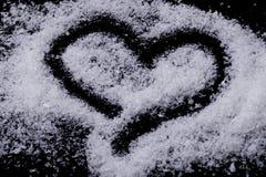 Corazón dibujado con nieve en fondo negro foto de archivo