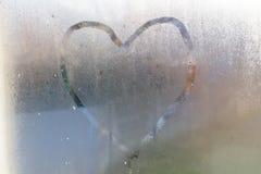 Corazón dibujado en la ventana de cristal empañada Foto de archivo libre de regalías