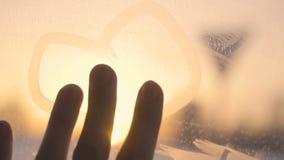 Corazón dibujado tacto de la mano de la mujer de la muchacha en ventana congelada en la cámara lenta del invierno de la puesta de metrajes