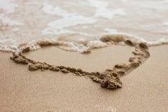 Corazón drenado en la arena Foto de archivo