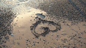 Corazón en arena en la orilla de mar en día soleado