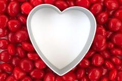 Corazón en blanco rodeado con el caramelo rojo Fotos de archivo