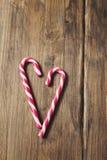 Corazón en honor del día del ` s de la tarjeta del día de San Valentín hecho del bastón de caramelo en un fondo de tablones de ma Foto de archivo