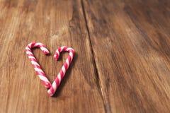 Corazón en honor del día del ` s de la tarjeta del día de San Valentín hecho del bastón de caramelo en un fondo de tablones de ma Fotografía de archivo libre de regalías