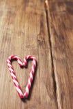 Corazón en honor del día del ` s de la tarjeta del día de San Valentín hecho del bastón de caramelo en un fondo de tablones de ma Fotos de archivo