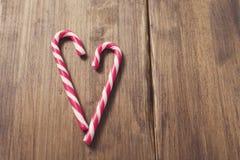 Corazón en honor del día del ` s de la tarjeta del día de San Valentín hecho del bastón de caramelo en un fondo de tablones de ma Fotografía de archivo