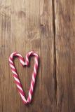 Corazón en honor del día del ` s de la tarjeta del día de San Valentín hecho del bastón de caramelo en un fondo de tablones de ma Imagen de archivo
