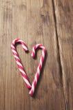 Corazón en honor del día del ` s de la tarjeta del día de San Valentín hecho del bastón de caramelo en un fondo de tablones de ma Imágenes de archivo libres de regalías