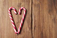 Corazón en honor del día del ` s de la tarjeta del día de San Valentín hecho del bastón de caramelo en un fondo de tablones de ma Fotos de archivo libres de regalías