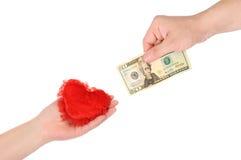 Corazón en mano femenina y mano con un billete de banco. Fotografía de archivo libre de regalías