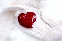Corazón en manos en concepto que se calienta de la nieve Fotografía de archivo