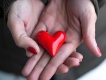 Corazón en manos de la mujer Foto de archivo