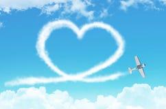 Corazón figurado del amor de un aeroplano blanco del luz-motor del rastro del humo entre las nubes imagenes de archivo