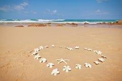 Corazón floral en la arena. Imagen de archivo libre de regalías