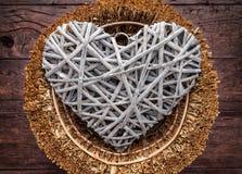 Corazón grande en una cesta en fondo de madera Fotos de archivo