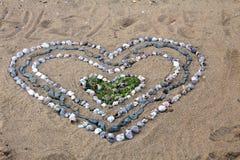 Corazón grande hecho de pequeñas conchas marinas en la playa arenosa en la playa del Mar Negro en Obzor, Bulgaria Foto de archivo libre de regalías