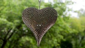 Corazón grande hecho del hierro con los modelos bajo la forma de colgante de las flores almacen de video